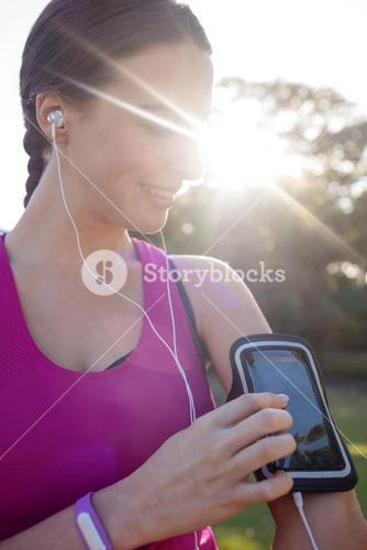 Smiling female jogger listening to music on mobile phone