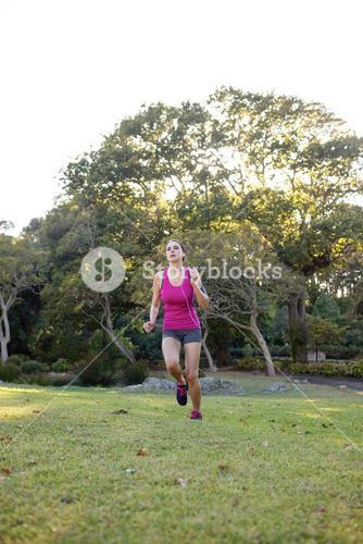Female jogger listening to music while jogging