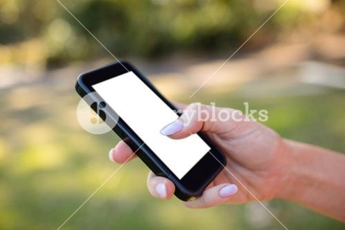 Womans hand using a mobile phone in the park