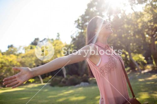 Carefree woman standing with her arms spread in the park