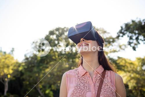 Smiling woman using a VR headset in the park