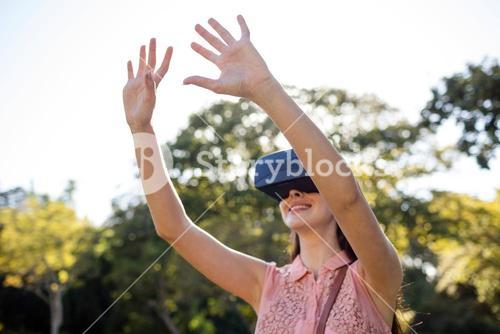Smiling woman raising her hands while using a VR headset in the park