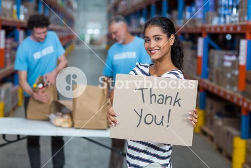 Portrait of woman holding sign boards with thank you message