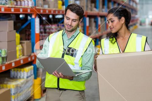 Warehouse workers working on laptop