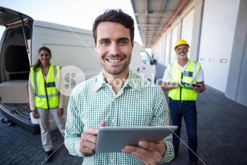 Portrait of manager using digital tablet and workers standing in background