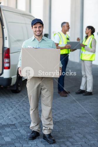 Portrait of delivery man carrying cardboard box