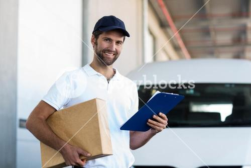 Portrait of delivery man holding a parcel and clipboard