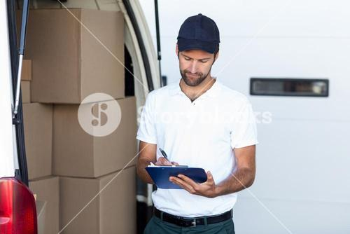 Delivery man writing on clipboard while standing next to his van