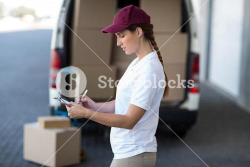 Delivery woman writing on clipboard while standing next to van