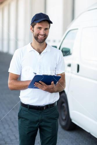 Portrait of delivery man holding a clipboard next to his van