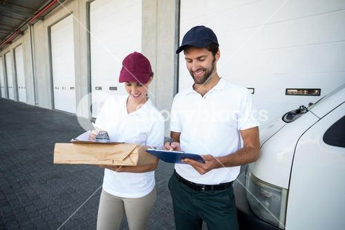 Happy delivery man and woman writing on clipboard next to van