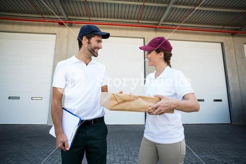 Happy delivery man and woman standing with clipboard and parcel