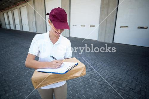 Smiling delivery woman writing on clipboard