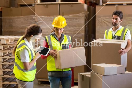 Manager noting on digital tablet while workers carrying cardboard boxes