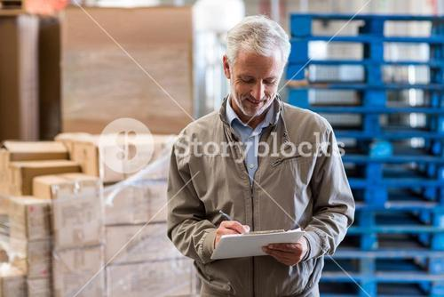 Smiling warehouse manager holding a clipboard