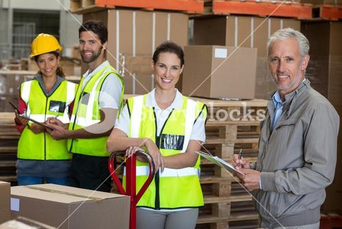 Portrait of warehouse manager and workers preparing a shipment