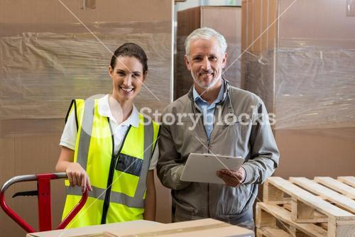 Portrait of warehouse manager and worker preparing a shipment