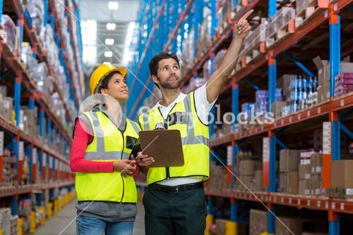Male and female worker checking inventory