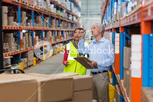 Warehouse manager and female worker interacting while checking inventory