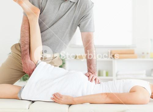 Chiropractor is stretching a womans leg