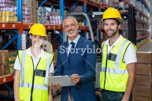 Portrait of wrehouse manager and co-workers standing with clipboard