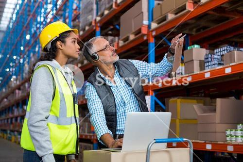 Warehouse manager and female worker interacting while using laptop