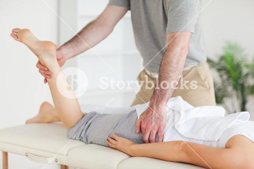Chiropractor stretches a female customers leg