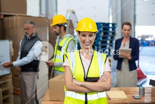 Portrait of female warehouse worker standing with arms crossed