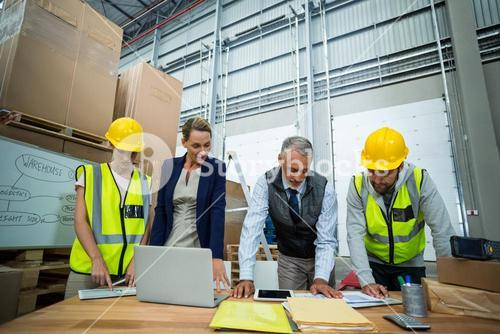 Warehouse workers and managers working in warehouse