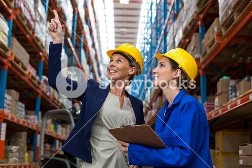 Warehouse manager and worker checking the inventory