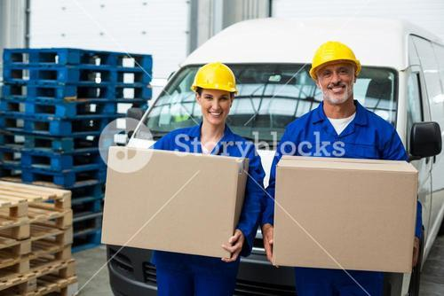 Portrait of delivery workers carrying cardboard box