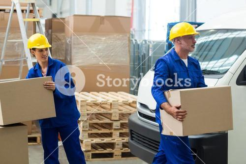 Delivery workers unloading cardboard boxes from pallet jack