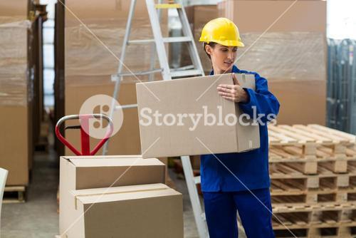 Delivery worker unloading cardboard boxes from pallet jack