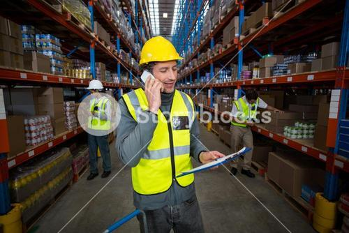 Warehouse worker talking on mobile phone and holding clipboard