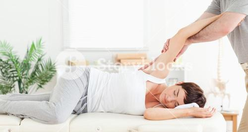 Chiropractor stretching womans arm