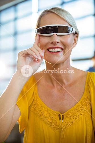 Female business executive using virtual reality video glasses