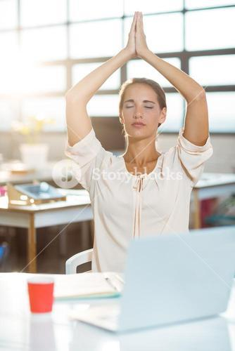 Female business executive performing yoga