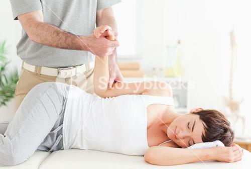 Chiropractor stretches a customers arm