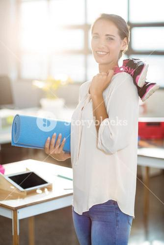 Female business executive holding exercise mat and shoes