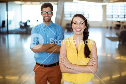 Business executive and co-worker standing with arms crossed