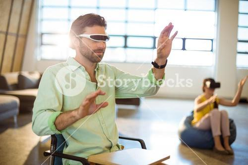 Male business executive using virtual reality video glasses