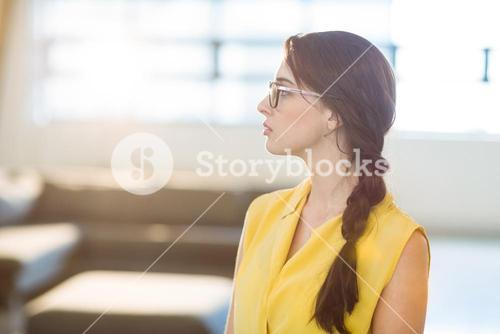 Thoughtful female business executive standing