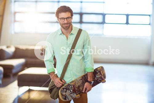 Male business executive standing with skateboard