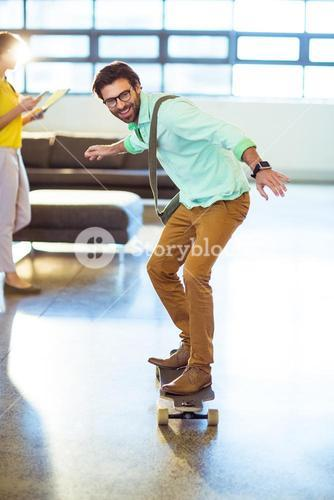 Male business executive riding skateboard