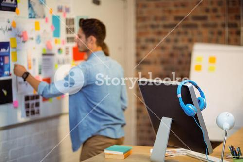 Business executive putting sticky notes on whiteboard