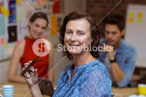 Smiling businesswoman holding spectacles