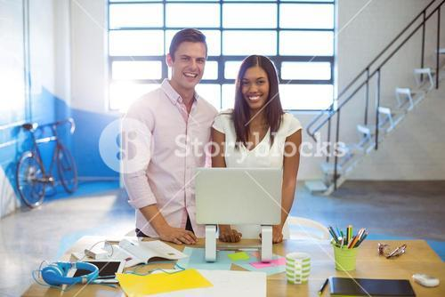 Business people standing with a laptop