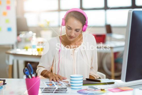 Graphic designer listening to music and looking at color swatch