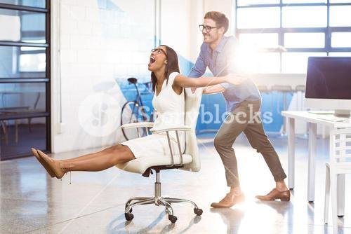 Business executive pushing businesswoman in office chair