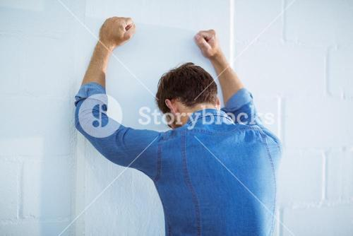 Tired businessman leaning on wall